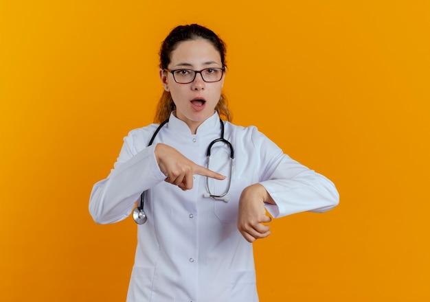 Jonge vrouwelijke arts die medische mantel en stethoscoop met bril draagt die geïsoleerdt het gebaar van de polsklok toont