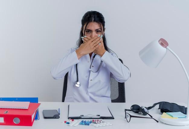 Jonge vrouwelijke arts die medische mantel en stethoscoopzitting bij bureau met medische hulpmiddelen draagt die behandelend mond met geïsoleerde handen kijkt