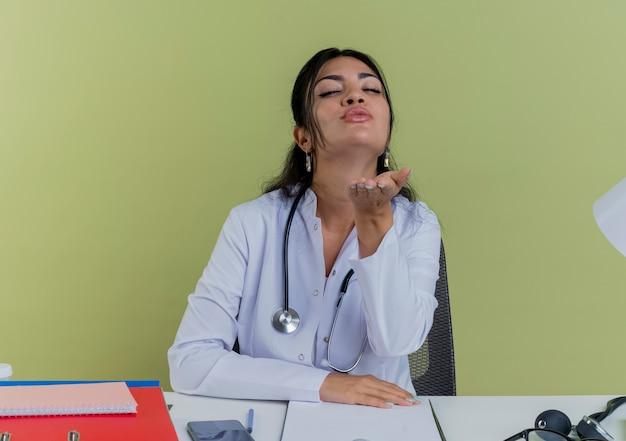Jonge vrouwelijke arts die medische mantel en stethoscoopzitting bij bureau met medische hulpmiddelen draagt die het verzendende geïsoleerde kus van de slagkus kijkt
