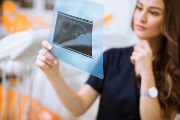 Jonge vrouwelijke arts die met beschermende handschoenen röntgenfoto in het tandartsbureau onderzoeken