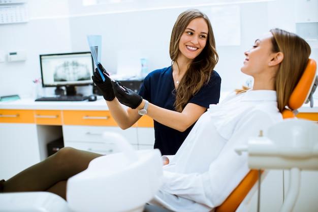 Jonge vrouwelijke arts die met beschermende handschoenen röntgenfoto met haar patiënt in het tandartsbureau onderzoeken