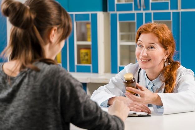 Jonge vrouwelijke arts die met de patiënt spreekt