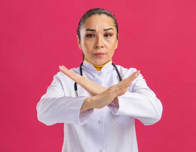 Jonge vrouwelijke arts die met ernstig gezicht een stopgebaar maakt dat de handen kruist