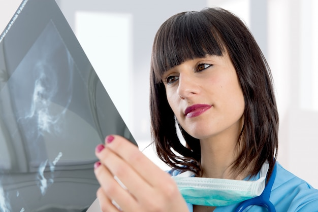 Jonge vrouwelijke arts die met stethoscoop patiëntenröntgenstraal bekijkt