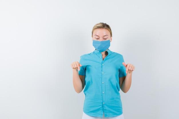 Jonge vrouwelijke arts die naar beneden wijst in medisch uniform, masker en verbaasd kijkt