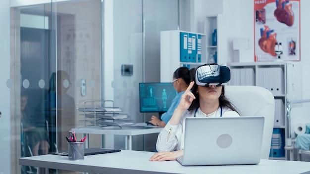 Jonge vrouwelijke arts die onderzoek doet in de geneeskunde met een virtual reality-headset op in een moderne privékliniek. verpleegkundige die op de achtergrond werkt en ander medisch personeel dat langsloopt. zorgsysteem ziekenhuis