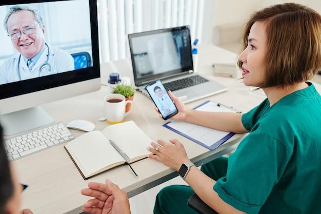 Jonge vrouwelijke arts die online conferentie heeft met collega's en moeilijke ziektebehandeling bespreekt