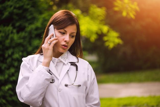 Jonge vrouwelijke arts die op de telefoon in openlucht spreekt