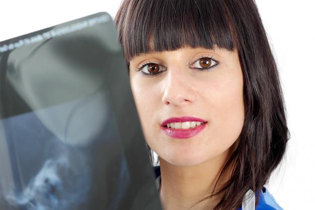 Jonge vrouwelijke arts die patiënten x ray bekijkt