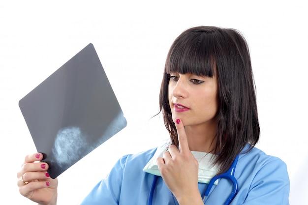 Jonge vrouwelijke arts die patiëntenröntgenstraal bekijkt