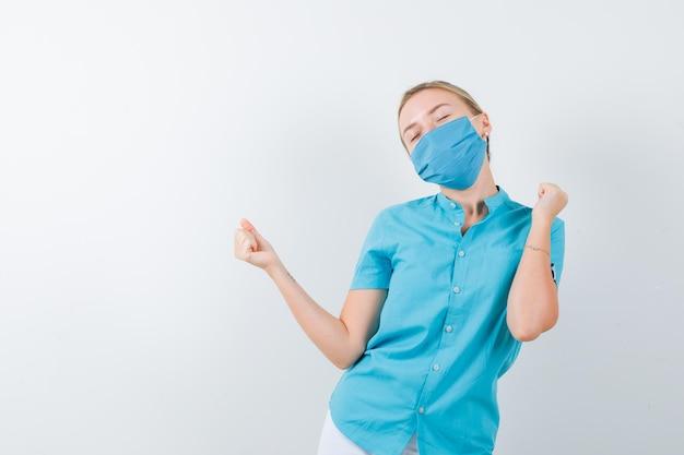 Jonge vrouwelijke arts die winnaargebaar in overhemd toont en gelukkig kijkt