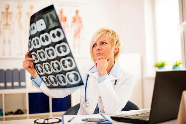 Jonge vrouwelijke arts die x-ray beeld bestudeert