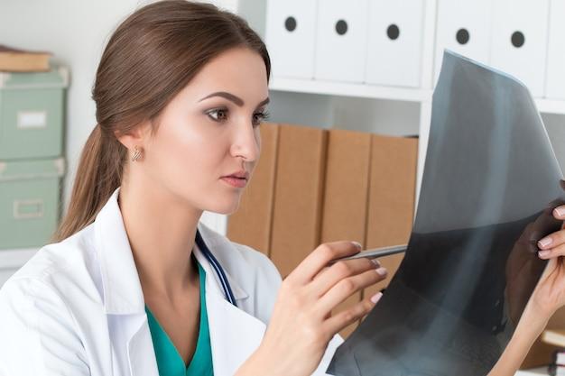 Jonge vrouwelijke arts die x ray beeld van de longen bekijkt
