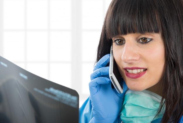 Jonge vrouwelijke arts die x-ray patiënten en het roepen bekijkt
