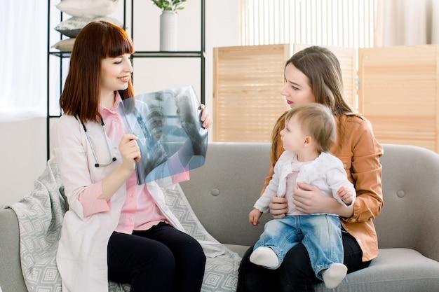 Jonge vrouwelijke arts die xray beeld toont aan jonge moeder met vrolijke dochter in kliniek