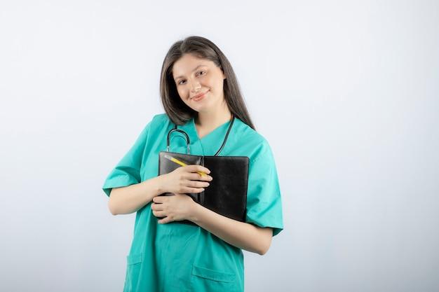 Jonge vrouwelijke arts die zich met notitieboekje en potlood bevindt.