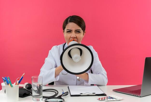 Jonge vrouwelijke arts draagt ?? medische mantel met stethoscoop zittend aan een bureau werken op computer met medische hulpmiddelen spreekt op luidspreker op geïsoleerde roze muur met kopie ruimte