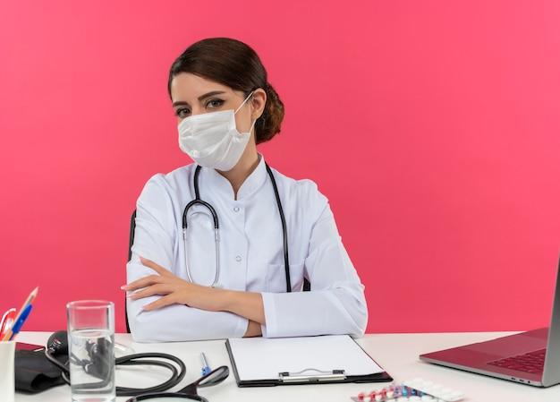 Jonge vrouwelijke arts draagt ?? medische mantel met stethoscoop zittend aan een bureau werken op de computer met medische hulpmiddelen handen kruisen op geïsoleerde roze muur met kopie ruimte