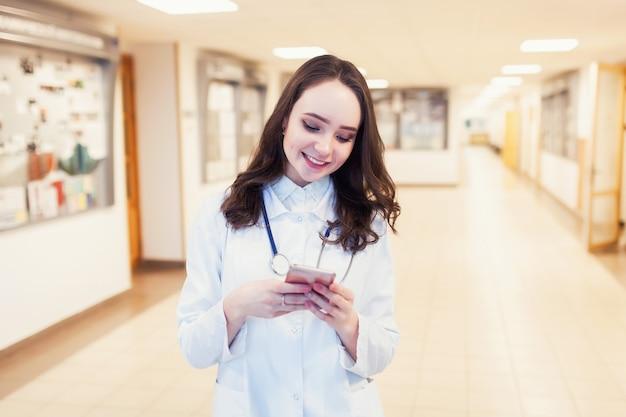 Jonge vrouwelijke arts glimlachend in een witte jas met een telefoon in handen. mooie medische student kijkt naar de tablet.