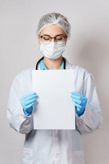 Jonge vrouwelijke arts houdt papier vast en houdt een vel blanco wit papier vast