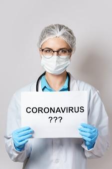Jonge vrouwelijke arts houdt papier vast met de coronavirus-letters