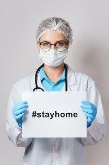 Jonge vrouwelijke arts houdt papier vast met de hashtag #stayhome