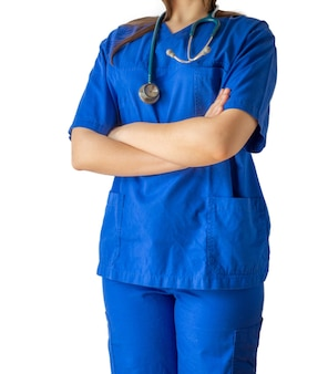 Jonge vrouwelijke arts in een blauw medisch uniform dat zich vol vertrouwen met gekruiste handen bevindt