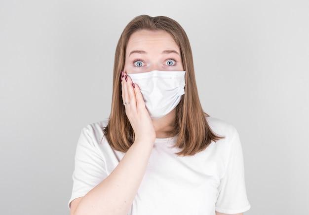Jonge vrouwelijke arts in een medisch masker kijkt met verbazing in de camera en houdt haar gezicht met haar hand vast. na het oplopen van covid 19, griep en seizoensgebonden verkoudheden.