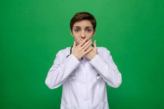 Jonge vrouwelijke arts in een witte jas met een stethoscoop die er geschokt uitziet en de mond bedekt met handen