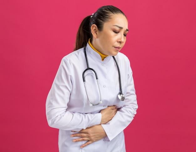 Jonge vrouwelijke arts in een witte medicijnjas met een stethoscoop om de nek die haar buik aanraakt en er onwel uitziet, pijn voelt die over een roze muur staat