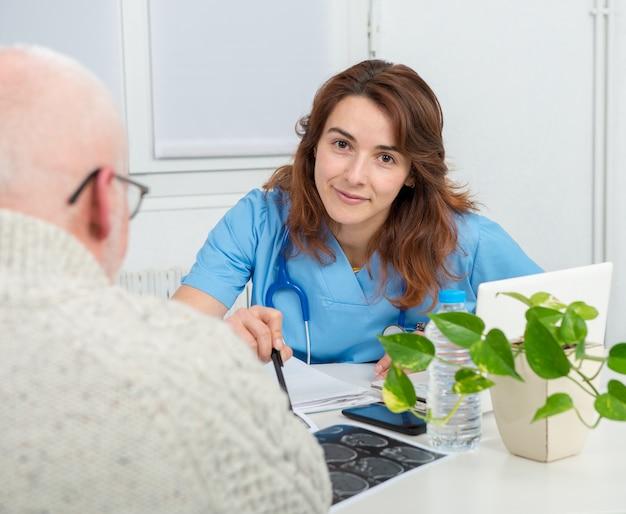 Jonge vrouwelijke arts in het kantoor met haar patiënt