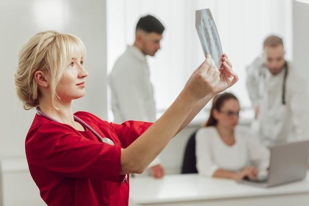 Jonge vrouwelijke arts in het ziekenhuis die x-ray bekijken
