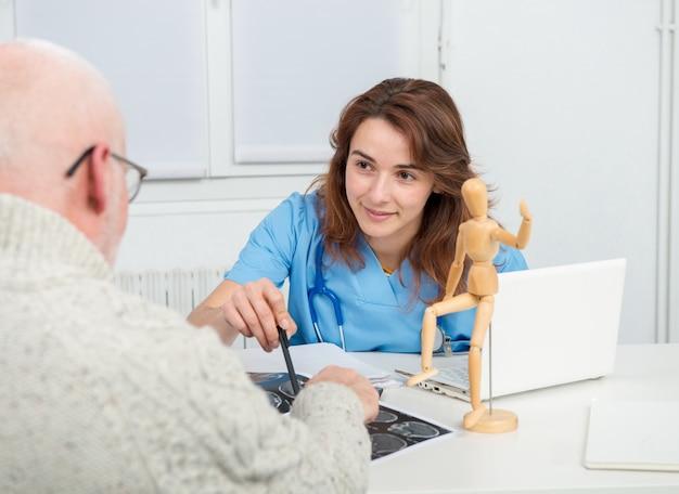 Jonge vrouwelijke arts in kantoor met haar patiënt
