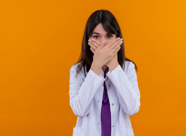 Jonge vrouwelijke arts in medisch gewaad met stethoscoop kruist handen en sluit mond op geïsoleerde oranje muur