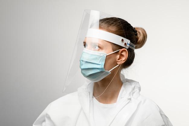 Jonge vrouwelijke arts in medisch masker en beschermend schild op haar hoofd dat weg eruit ziet.