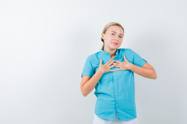 Jonge vrouwelijke arts in medisch uniform, masker hand in hand op de borst en hoopvol kijkend?