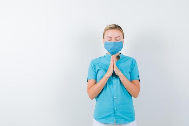 Jonge vrouwelijke arts in medisch uniform, masker met gevouwen handen in een smekend gebaar