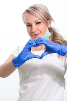 Jonge vrouwelijke arts in tandarts in wit medisch eenvormig en gezichtsmasker die en positief op wit geïsoleerde achtergrond glimlachen stellen