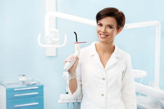Jonge vrouwelijke arts in tandartsbureau. mooie glimlachende vrouw die in witte laboratoriumlaag blauw tand het genezen licht houden. tandarts. stomatology