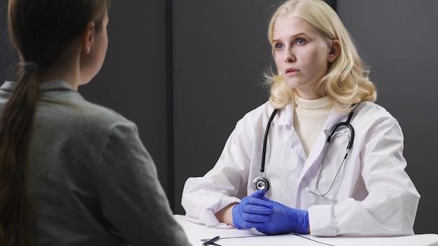 Jonge vrouwelijke arts in wit medisch uniform met behulp van klembord levert geweldig nieuws, bespreking van resultaten of symptomen met vrouwelijke patiënt