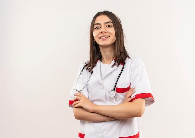 Jonge vrouwelijke arts in witte jas die met een stethoscoop om haar hals naar voren kijkt met hand op borst die zelfverzekerd over witte muur kijkt