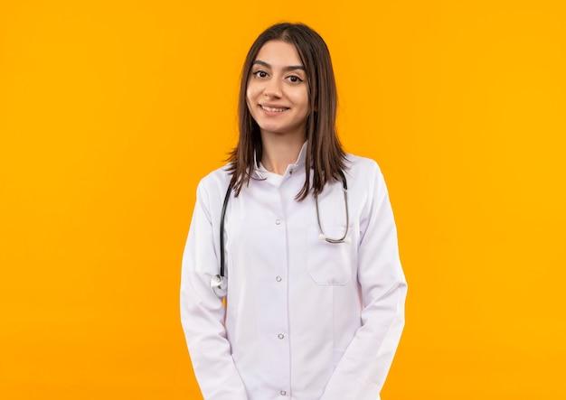 Jonge vrouwelijke arts in witte jas die met een stethoscoop om haar hals naar voren kijkt met zelfverzekerde glimlach die zich over oranje muur bevindt