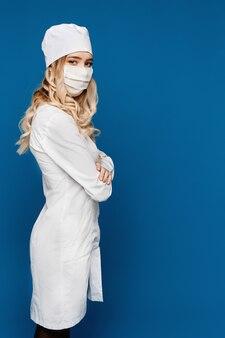Jonge vrouwelijke arts in witte jas en medische masker poseren door een zijde