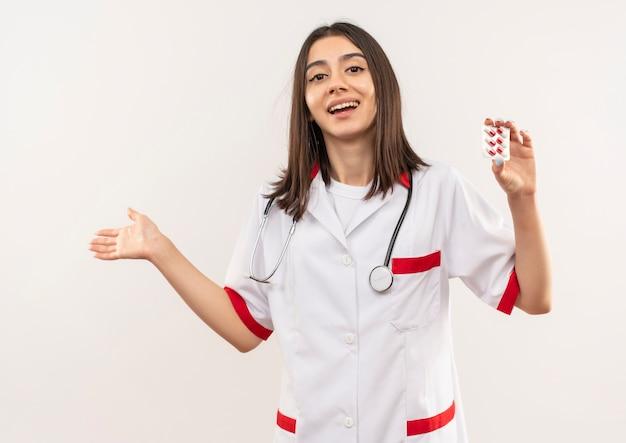Jonge vrouwelijke arts in witte jas met een stethoscoop om haar nek die blister met pillen toont die met de arm van de hand naar de zijkant wijzen, blij en verbaasd staande over witte muur