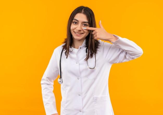 Jonge vrouwelijke arts in witte jas met een stethoscoop om haar nek die met de vinger naar haar oog richt die zich over oranje muur glimlachen