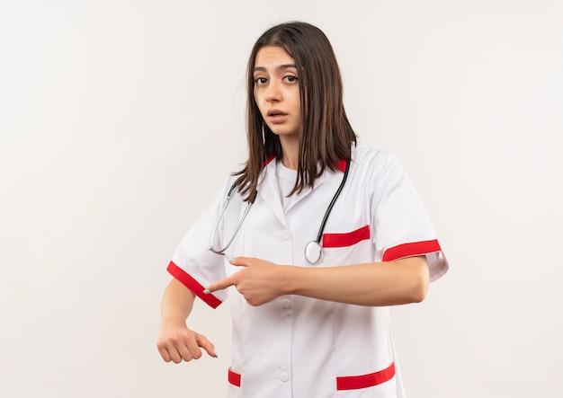 Jonge vrouwelijke arts in witte jas met een stethoscoop om haar nek die naar haar arm wijst en eraan herinnert dat tijd op zoek bezorgd over een witte muur