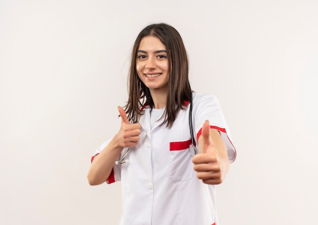 Jonge vrouwelijke arts in witte jas met een stethoscoop om haar nek die vrolijk glimlachend duimen toont die zich over witte muur bevinden