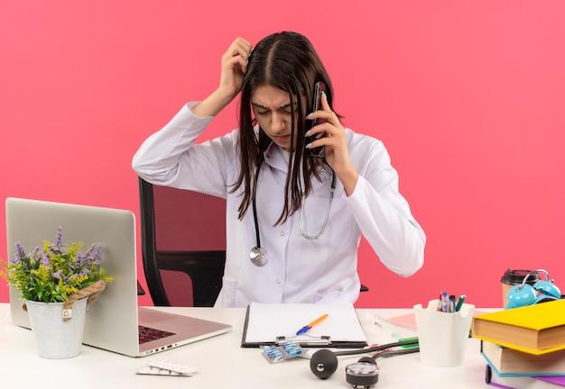 Jonge vrouwelijke arts in witte jas met een stethoscoop om haar nek kijkt verward tijdens het praten op de mobiele telefoon haar hoofd krabben zittend aan tafel met laptop over roze muur