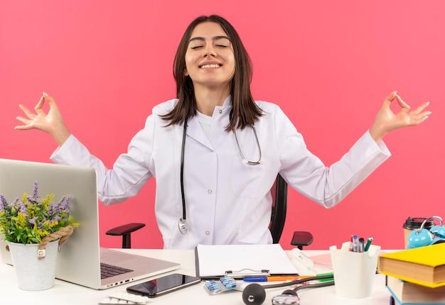 Jonge vrouwelijke arts in witte jas met een stethoscoop om haar nek ontspannen met gesloten ogen meditatie gebaar maken met vingers zittend aan tafel met laptop over roze muur