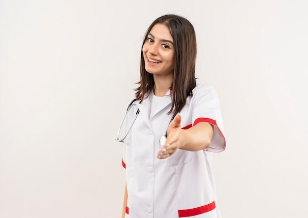 Jonge vrouwelijke arts in witte jas met een stethoscoop om haar nek op zoek naar de voorkant glimlachend vriendelijk aanbiedende hand staande over witte muur